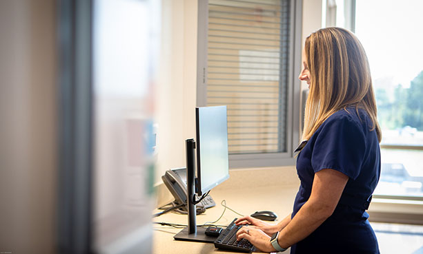 nurse standing at computer