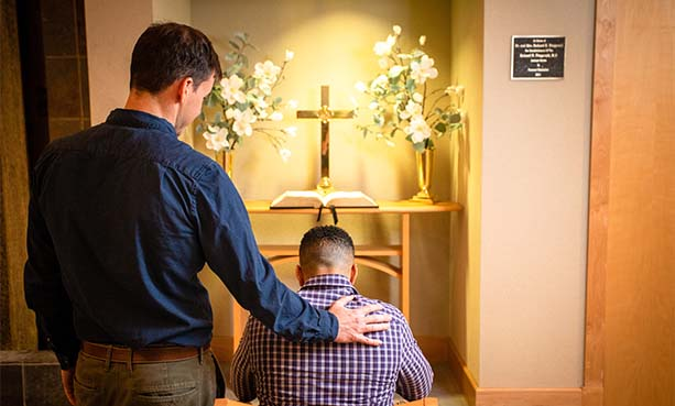 pastor praying with patient
